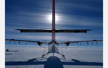 Photo of a Twin Otter aircraft silhouetted by the sun.