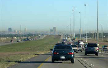 Photo of cars on a highway with smog in the distance.