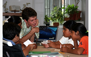 Teacher and students around a computer monitor.