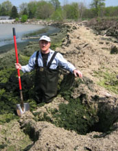 Researcher With shovel knee deep in an algae accumulation along Lake Erie