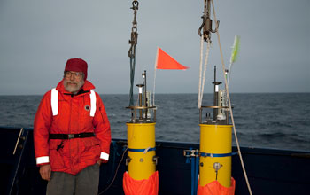 Photo of scientist Eric D'Asaro standing on deck with robotic floats he developed.