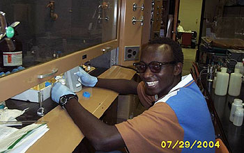 student works with lab equipment under hood