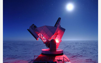 Photo of the South Pole Telescope illuminated by red lights.