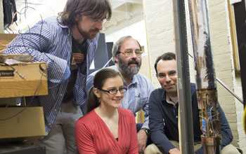 Photo of  researchers examining a tubular structure to measure the magnetic charge of an antiproton.