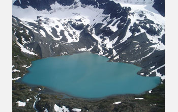 Photo of sharp-crested ridges of glacial debris that descend into Upper Greyling lake in Alaska.