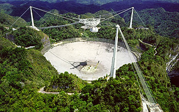 White telescope floats over concrete crater, lush hills in background.