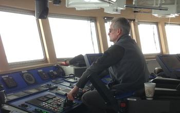 Capt. Dan Hobbs in front of operating controls of the ship