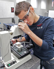 a student uses an industrial microscope
