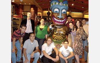 Photo of nine undergraduate students and their professor posing by a statue.