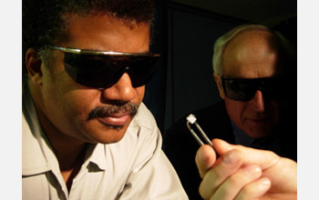 Photo of Neil deGrasse Tyson examining an unpolished man-made diamond, fresh out of the grower.