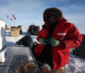 Photo of Slawek Tulaczyk installing a precision GPS sensor for monitoring a subglacial lake.