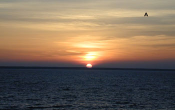 "A picture of the setting sun off the coast of Estonia and the letter ""A."""