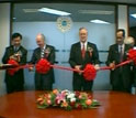Four officials prepare to cut a red ribbon at the ribbon-cutting ceremony