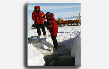 Biology course students collect water samples below the McMurdo Sound sea ice.