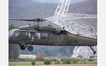 Photo of a Blackhawk helicopter lifting off in front of the Robert C. Byrd Green Bank Telescope.