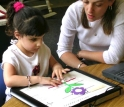 A kindergartner examines a Talking Tactile Tablet picture of a flower.