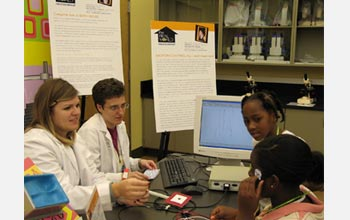 Photo of graduate students assisting a visitor in applying electrodes measuring eye movements.