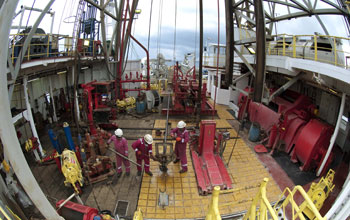 Photo of scientists and engineers working on the rig floor aboard the drill ship JOIDES Resolution.