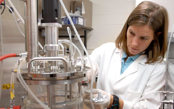 Photo of grad student Natasha Mallette working with a fermentation system for converting biomass.