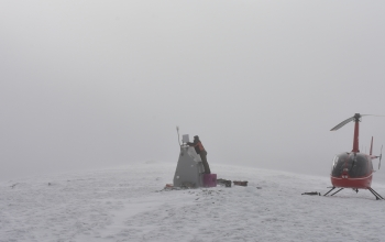 Field operations manager Ryan Bierma makes last adjustments to station C19K as a blizzard rolls in.