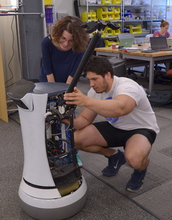 Two students add a manipulating arm to a robot base