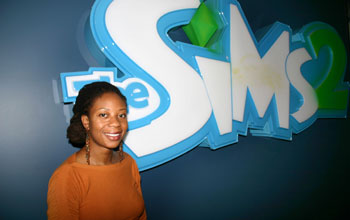 A young woman standing in front of a sign with the text The SIMS.