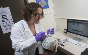 Sarah Laszlo prepares a subject to measure brain activity using electroencephalography (EEG).