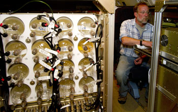 Air-sampling flasks used during HIPPO flights and researcher Andy Watt on the plane