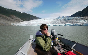 Photo of researcher Eran Hood operating the motor in a boat with Mendenhall Glacier in background.
