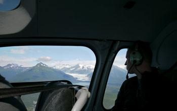 Photo of scientist Robert Spencer looking down on Mendenhall Glacier from a helicopter.