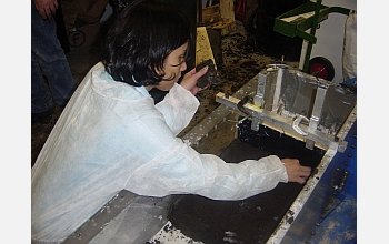 A team member lays peat from New Orleans into the centrifuge sample chamber.