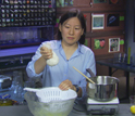 Photo of Julie Yu making fresh cheese from milk and lemon juice.