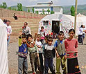 Children stand outside their makeshift classroom in the post-earthquake military tent city.