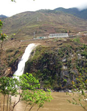 Small hydropower plant discharges water from tributary to main channel of the Nu River.