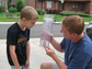 man and child look at a rain gauge in a driveway