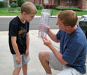 Photo of a father and son measuring rainfall data in Concord, N.C.