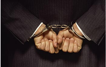 Photo of a man's hands cuffed behind his back.