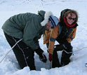 Photo shows 2 people collecting sediment core from a lake on Baffin Island.