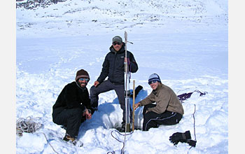 Photo showing three people and a lake sediment core.