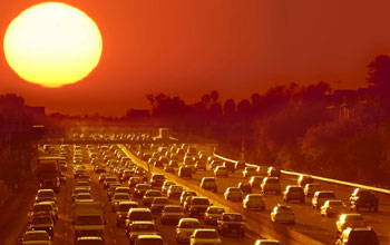 Photo of sun shining over cars in busy traffic on a highway