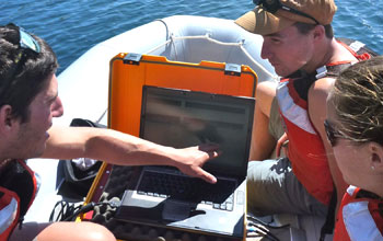 Student researchers in a boat use acoustic imaging to select a lake site