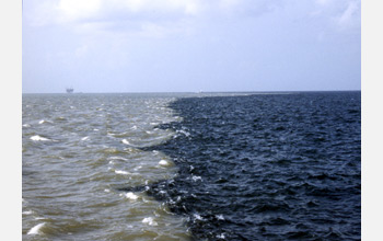 Photo of the sediment laden Mississippi River on left and Gulf of Mexico on the right.