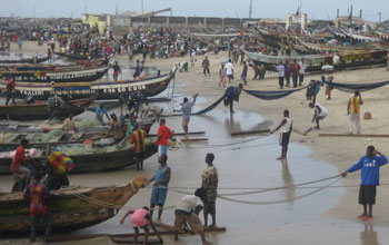 Photo of African fishermen with their boats on the beach.