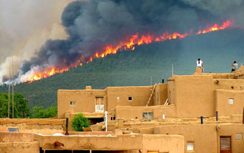 Photo of a wildfire over pine forested hills in background with houses in foreground in New Mexico.