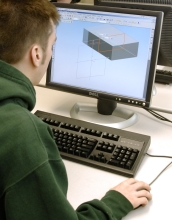 A male college student works at a computer with a 3-D image of a rectangular object on the screen.