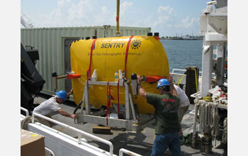 Photo of an autonomous underwater vehicle being loaded onto a research vessel.