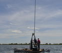 Scientists in a boat collecting a sediment core