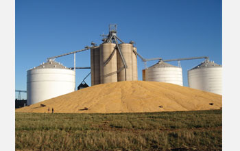 Photo of silos with pile of corn in the foreground.
