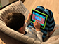 little boy sitting on a sofa playing with a tablet