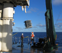 Photo of scientists on a research vessel sampling the South Pacific Ocean for microbes.
